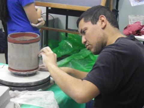 A Master's student painting his replica of a Mayan vessel